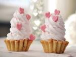 Dos ricos pasteles con corazones rosas