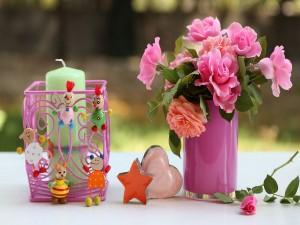 Vela junto a un jarrón con rosas