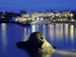 Roca iluminada por las luces del pueblo pesquero