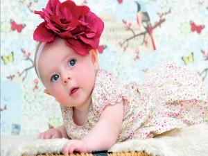 Bebé con una gran flor en la cabeza