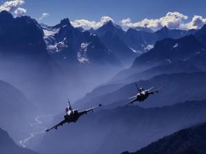 Dos aviones de combate volando entre montañas