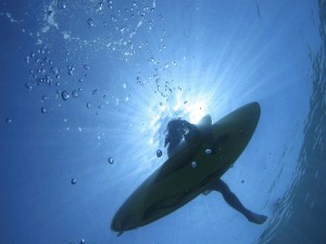 Surfista sentado sobre su tabla en la superficie del agua