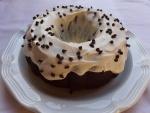 Un rico bundt cake cubierto de crema y pepitas de chocolate