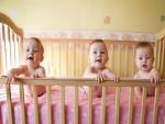 Tres bebas felices en una cuna