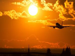 Avión despegando hacia el sol