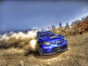 Subaru azul derrapando en la arena