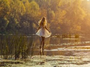Mujer con vestido blanco caminando sobre el agua