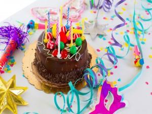 Pastel de chocolate con velas de cumpleaños y serpentinas