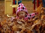 Niña jugando con las hojas de otoño