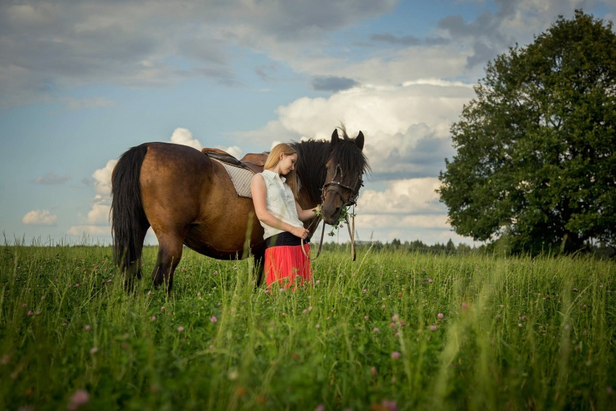 Mujer acariciando a un caballo que come hierba fresca