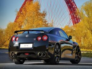 Nissan GT-R negro junto a unos árboles en otoño