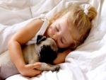 Niña durmiendo junto a su perrito