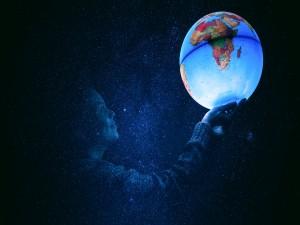 Mujer en la oscuridad sosteniendo la Tierra en sus manos