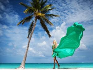 Elegante mujer caminando por la arena de una playa