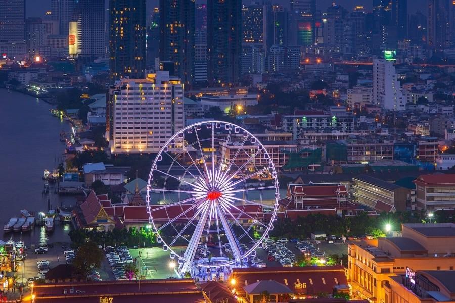 Vista nocturna de una noria y la ciudad de Bangkok