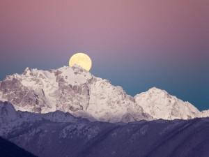 Gran luna tras la cima de una montaña
