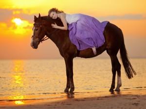 Bella mujer tendida sobre un caballo