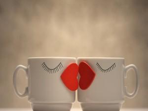 Dos tazas con corazones rojos besándose