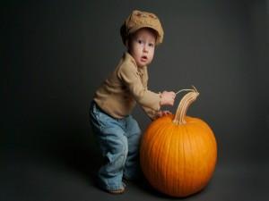 Niño junto a una gran calabaza