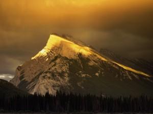 Sol iluminando la cima de una montaña
