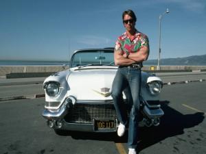 Arnold Schwarzenegger sentado en un Cadillac
