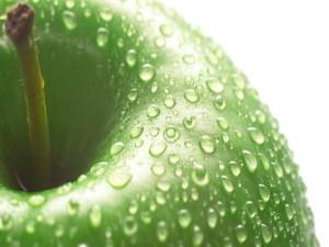Sabrosa manzana verde con gotitas de agua