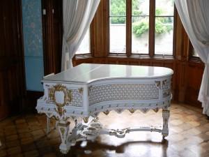 Elegante piano blanco frente a una ventana