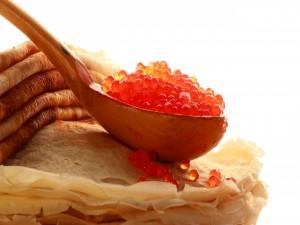 Cuchara con caviar rojo sobre unos crepes