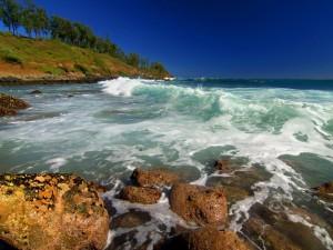Las revueltas olas del mar lavan unas rocas en la costa
