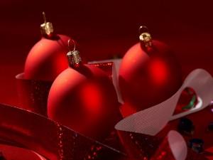Bolas rojas de Navidad envueltas en cinta de color rojo brillante