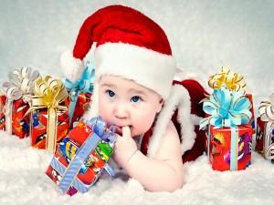 Bebé junto a unos regalos de Navidad
