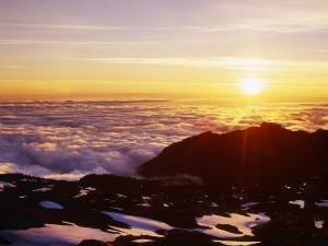 Sol sobre las nubes y montañas
