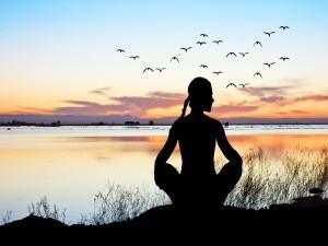 Silueta de mujer practicando yoga frente al agua