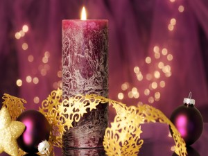Vela y bolas de Navidad junto a una cinta dorada