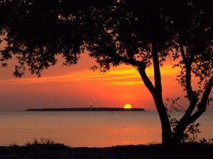 Faro y sol vistos desde la costa
