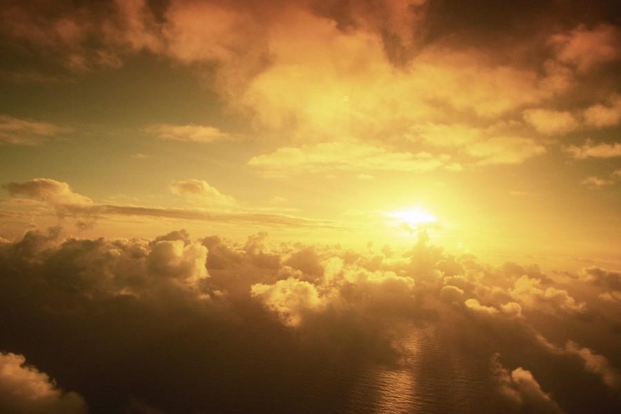 Sol brillando sobre mar y nubes