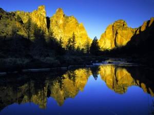Montañas rocosas reflejadas en el río