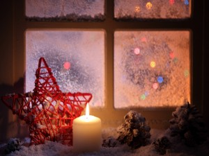 Vela y estrella de Navidad junto a una ventana