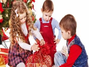 Niños abriendo regalos en las fiestas navideñas