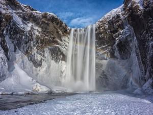 Arcoíris sobre una cascada en invierno
