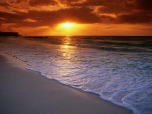 Sol iluminando la playa al amanecer