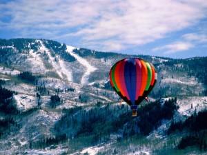 Globo volando sobre montañas nevadas