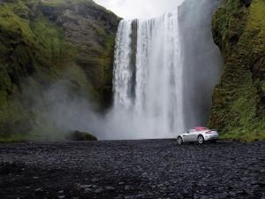 Aston Martin V8 Vantage Roadster frente a una cascada