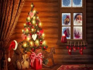 Papá Noel con los regalos asomado a una ventana