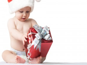 Bebé tratando de abrir un regalo de Navidad