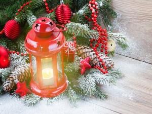 Farol con una vela encendida junto a un árbol de Navidad