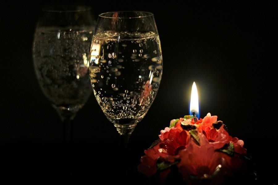 Vela encendida junto a unas copas de champán