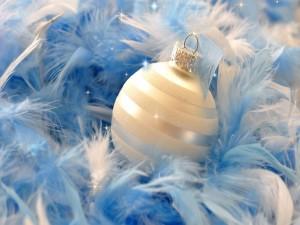 Bola blanca de Navidad sobre plumas azules