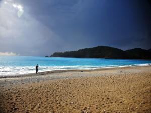 Persona con una caña de pescar caminando por la orilla del mar