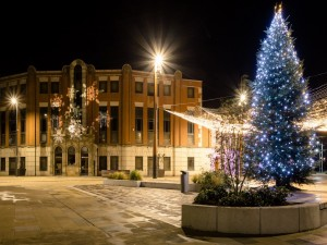 Árbol de Navidad iluminado al anochecer en la ciudad